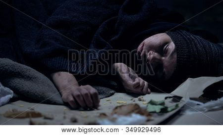 Homeless Vagabond Sleeping On Street Full Of Garbage, Poverty, Social Insecurity
