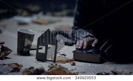 Homeless Refugee Holding Bible, Paper House And Cup Nearby, Searching For Home