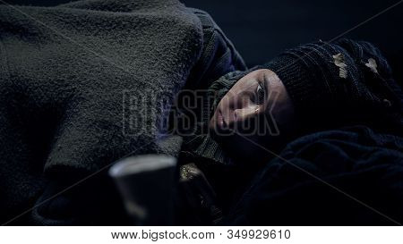 Crying Vagabond Lying On Floor And Looking To Camera, Beggar Paper Cup Nearby