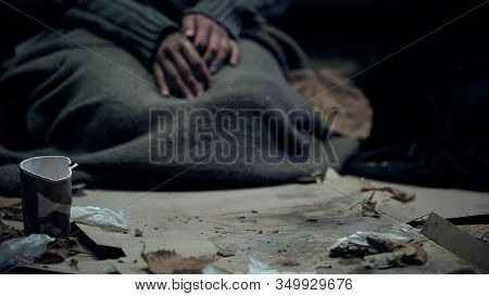 Vagabond Covered With Dirty Blanket Sitting On Carton, Living On Street, Refugee
