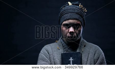 Female Vagabond With Bible In Hands Looking Camera On Dark Background, Hope