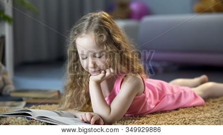 Curious Little Girl Lying On Floor, Reading Interesting Childrens Storybook