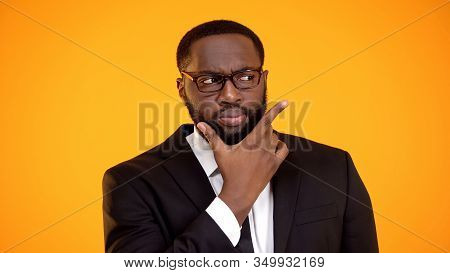 Suspicious African-american Businessman In Glasses Considering Options, Dilemma