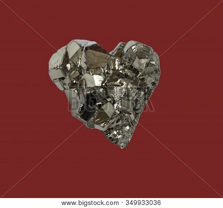 Mineral Pyrite In The Shape Of A Heart On A Dark Red Background