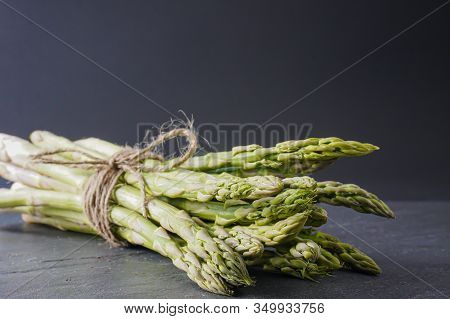 Close-up Of A Bundle Of Bright Green Asparagus Tied With Twine On A Gray Surface With Copy Space