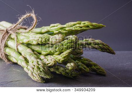 Close-up Of A Bundle Of Asparagus Tied With Twine On A Gray Slate Surface