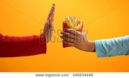 Female Hand Showing Stop Gesture On Yellow Background, Refusing Eat French Fries