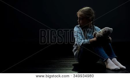 Little Girl With Teddy Bear Sitting Alone In Dark Room, Looking Around, Orphan