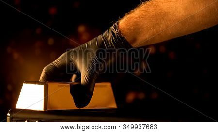 Hand In Glove Putting Gold Bullion, Evaluation Of Precious Metals, Pawnshop