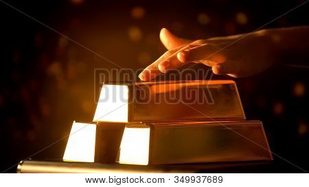 Female Hand Carefully Stroking Gold Bars, Gambling Or Wealth As Temptation