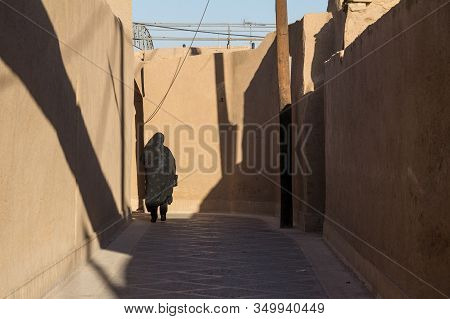 Shape Of A Woman Walking In The Streets Of Yazd, Iran, Passing Near A Traditional Clay Walls Of The