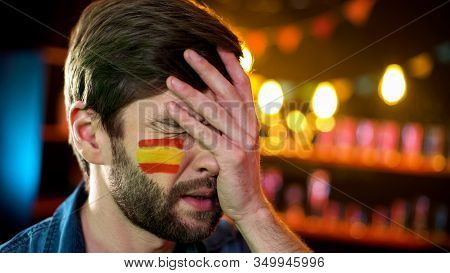 Nervous Fan With Spanish Flag On Cheek Making Facepalm Dissatisfied With Match