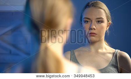 Teenage Girl Looking In Bathroom Mirror Reflection In Astonishment, Insecurities