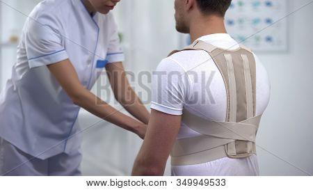 Orthopedist Applying Posture Control Shoulder Brace Male Patient, Healthcare