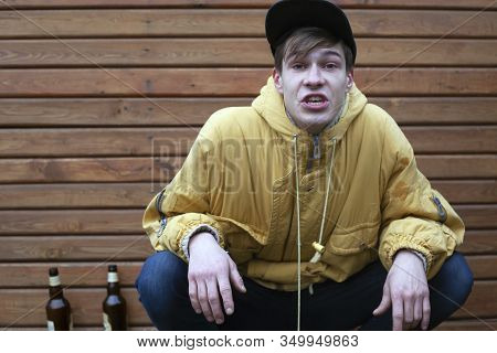 Cheeky Football Fan Got Drunk Beer. Stylish Young Guy In A Yellow Jacket With An Angry Face Swears.