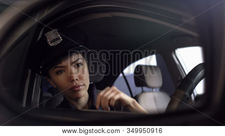 Asian Policewoman Looking At Car Mirror, Watching Risky Situation, Patrolling
