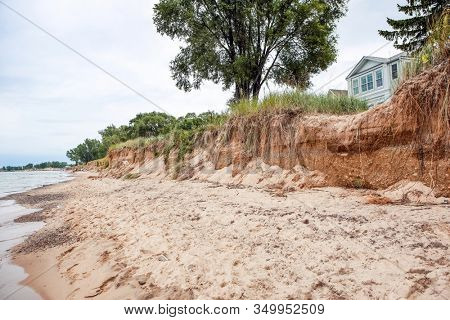 Beach houses on Lake Michigan, lake erosion dangerously close to the houses, focus on bluff in center of image