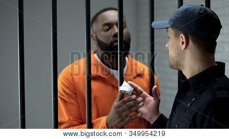 Prison Guard Giving Afro-american Imprisoned Male Dose Of Drugs Illegal Activity