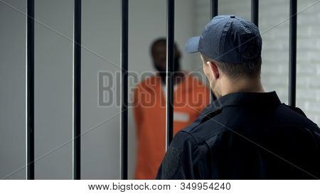 Warden Looking At Dangerous Criminal Standing In Cell, Life Sentence, Prison