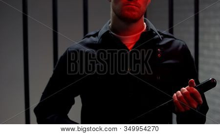 Aggressive Warden Holding Truncheon Standing Against Prison Cell, Red Lights