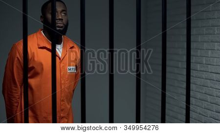 Indifferent Afro American Prisoner Praying To God In Cell, Waiting For Sentence