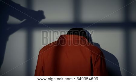 Prisoner Standing On Knees Near Wall, Warden Shadow With Truncheon, Harassment