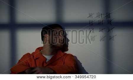 Male Prisoner Looking At Crossed Lines On Cell Wall, Serving Long Imprisonment