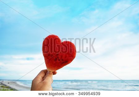 Happy Valentines Day, Valentines Day Beach, Hand Holding Heart Shaped Watermelon Against Blue Sky An