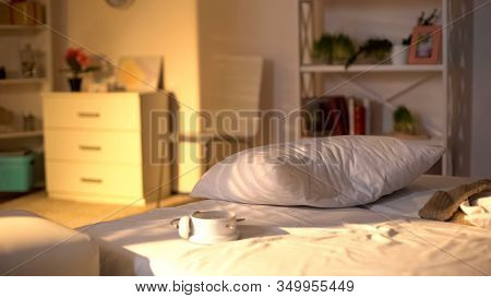 White Alarm Clock Lying On Messy Bed, Crumpled Bed Sheets, Oversleeping Concept