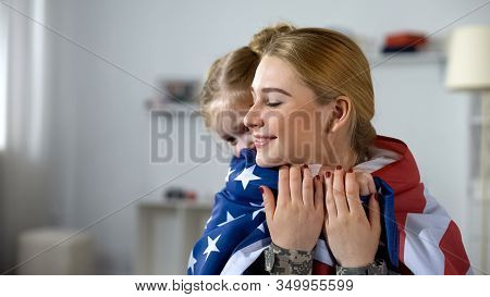 Little Daughter Hugging Soldier Mother With Us Flag, Happy With Homecoming