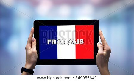 Female Hands Holding Tablet With French Word Against National Flag, Online App