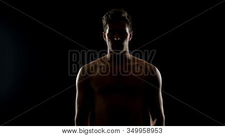Shadowed Topless Man Standing Against Black Background, Hopelessness Concept