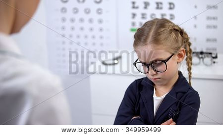 Female Doctor Putting Glasses On Disgruntled Girl, Child Feels Insecure, Upset