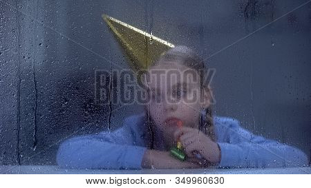 Sad Girl In Party Hat With Blower Behind Rainy Window, Forgotten By Parents