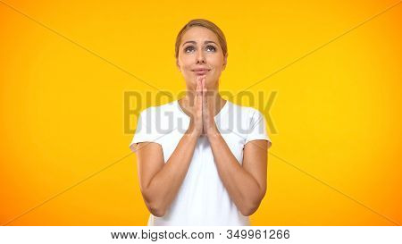Pretty Woman Making A Wish On Orange Background, Young Female Dreaming, Desire