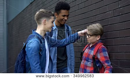 Cruel Teenage Boys Mocking Eyeglasses Of Younger Student, School Bullying