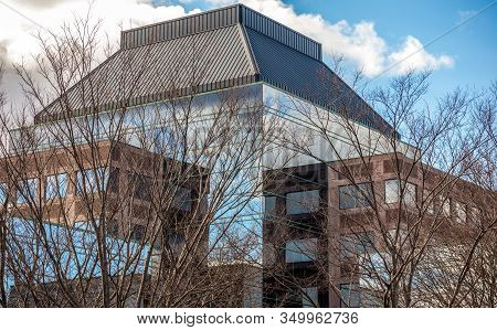 View Of The Top Of A Modern Business Corporate Building  And Bare Trees Against The Blue Sky In Quin