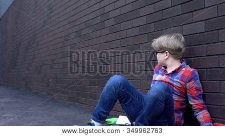 Abused Boy Sitting Helpless Near Wall, Depressed Victim Of Bullying Intimidation