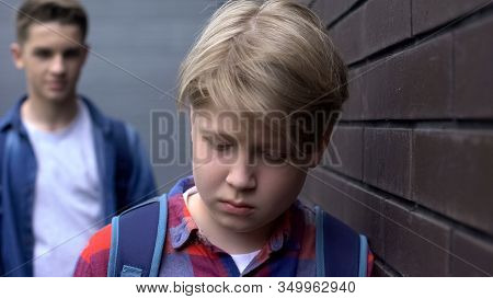 Bullied Boy Leaning Against Wall, Scared Of Offender Behind, Intimidation