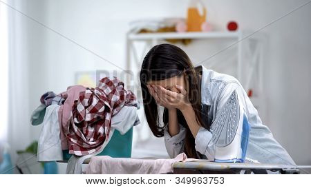 Stressed Housewife Ironing Clothes Leaning On Board And Crying, Domestic Work