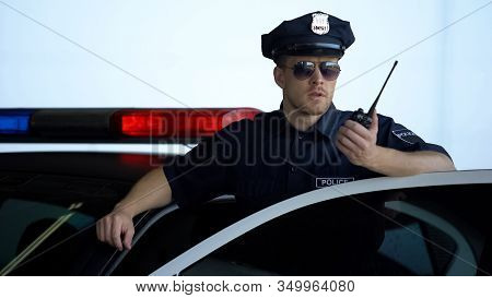 Officer Standing Near Police Car And Informing About Crime On Two-way Radio