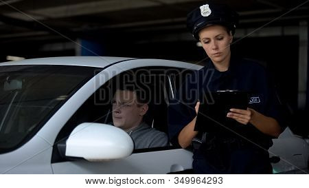 Female Officer Writing Traffic Ticket To Male Driver For Parking Violation, Fine