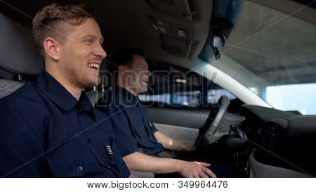 Cheerful Police Mates Laughing In Patrol Car During Daily Duty, Friendship