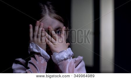 Scared Female Kid Peeping Through Fingers At Camera, Phobia And Anxiety Concept