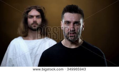 Sad Man With Messiah On Background Looking Camera, Spiritual Support, Faith
