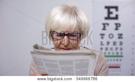 Senior Woman In Eyeglasses Reading Newspaper And Shaking Head, Cataract Risk