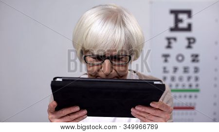 Female Retiree In Eyeglasses Holding Tablet And Shaking Head, Unable To Read