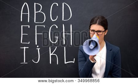 Nervous Teacher Shouting In Megaphone Claiming Attention, Alphabet On Blackboard