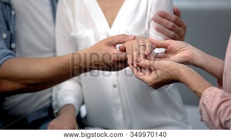 Man Holding Fiancee Hand With Engagement Ring, Showing To Mother, Happy Family