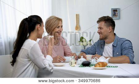 Young Couple And Mother-in-law Drinking Tea, Sincerely Laughing, Time Together